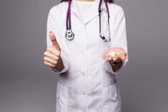 Hållande preventivpillerar för kvinnasjuksköterska i hand- och visningtummar som isoleras upp över grå bakgrund Arkivfoto