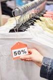 Hållande prislapp för hand med den 50% rabatten Arkivbild