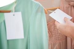 Hållande prislapp för kvinna på skjortan Arkivfoton