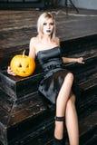 Hållande pumpor för ung blond kvinna för halloween Arkivbild