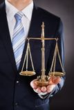 Hållande rättvisaskala för affärsman arkivfoto