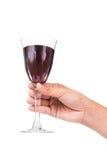 Hållande rött vin för hand i crystal exponeringsglas som är klart att rosta Royaltyfri Bild