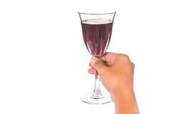 Hållande rött vin för hand i crystal exponeringsglas som är klart att rosta Royaltyfria Bilder