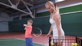 Hållande racket för kvinna som och för pojke har kurs på tennisbanan stock video