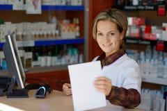Hållande recept för ung kvinnlig apotekare royaltyfri foto