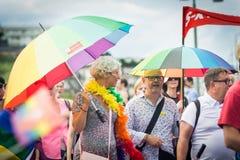 Hållande regnbågeparaplyer för folk i folkmassan under Stockholm Pride Parade Arkivfoton