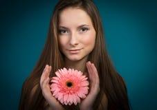 Hållande rosa färgblomma för attraktiv ung flicka Royaltyfri Fotografi