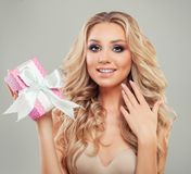 Hållande rosa gåva för förvånad kvinna med det silkeslena bandet Arkivbilder