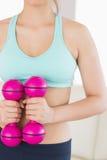Hållande rosa hantlar för färdig brunett Arkivfoton