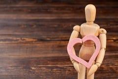 Hållande rosa hjärta för träskyltdocka royaltyfria foton