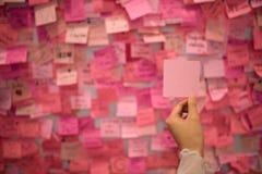 Hållande rosa klibbig anmärkning för kvinnahand Royaltyfria Foton