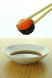 Hållande rulle för räkaäggsushi med pinnar och shoyusås Arkivfoton