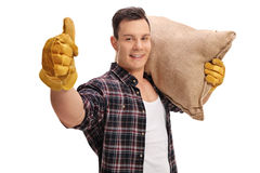 Hållande säckvävsäck för manlig bonde och ge sigtumme upp royaltyfria foton