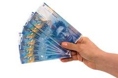 Hållande sedlar för hand av 100 schweizisk franc arkivbilder