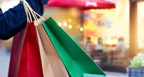 Hållande shoppingpåsar för kvinna på galleriagatabakgrund arkivfoton