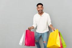 Hållande shoppingpåsar för lycklig afrikansk man Arkivbilder