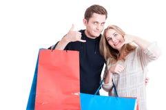 Hållande shoppingpåsar för par som gör att kalla gest Arkivbild