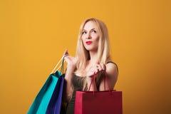 Hållande shoppingpåsar för ung blondy flicka som isoleras över gul bakgrund Royaltyfri Foto