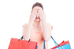 Hållande shoppingpåsar för ung dam som okontrollerat gör gest fotografering för bildbyråer