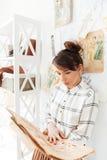 Hållande sketchbook för kvinnamodeformgivare, medan stå på hennes studio Arkivbild