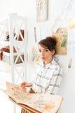 Hållande sketchbook för kvinnamodeformgivare, medan stå på hennes studio Royaltyfri Bild