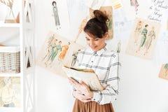Hållande sketchbook för kvinnamodeformgivare, medan stå på hennes studio Royaltyfri Foto