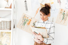 Hållande sketchbook för kvinnamodeformgivare, medan stå på hennes studio arkivfoto