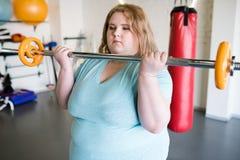 Hållande skivstång för sjukligt fet kvinna fotografering för bildbyråer