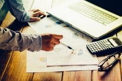 Hållande skrivbordsarbete för affärsman på tabellen och analyseringen Royaltyfri Bild