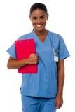 Hållande skrivplatta för aktiv kvinnlig sjuksköterska, på arbetsuppgiften Fotografering för Bildbyråer