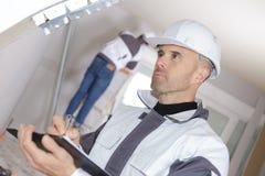 Hållande skrivplatta för arbetarinspektör på bakgrundskonstruktion Fotografering för Bildbyråer