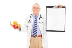 Hållande skrivplatta för doktor och en grupp av frukter Royaltyfri Fotografi