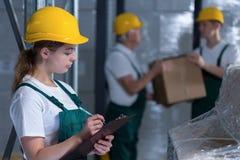 Hållande skrivplatta för kvinnlig fabriks- jobbare royaltyfria foton
