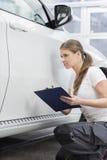 Hållande skrivplatta för kvinnlig mekaniker, medan den undersökande bilkroppen på reparationen shoppar arkivfoto