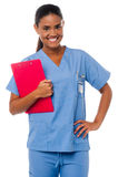 Hållande skrivplatta för kvinnlig sjuksköterska, på arbetsuppgiften Royaltyfria Bilder