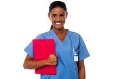 Hållande skrivplatta för kvinnlig sjuksköterska, på arbetsuppgiften Royaltyfri Bild