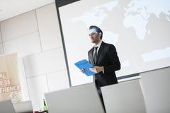 Hållande skrivplatta för säker affärsman, medan stå i seminariumkorridor Arkivbild