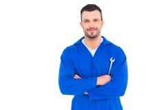 Hållande skruvnyckel för lycklig mekaniker på vit bakgrund arkivfoton