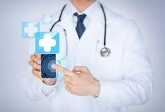 Hållande smartphone för doktor med läkarundersökningen app Royaltyfri Foto
