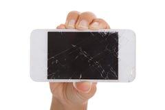 Hållande smartphone för hand med den spruckna skärmen Arkivbilder