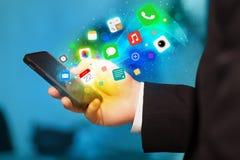 Hållande smartphone för hand med färgrika app-symboler Arkivbild