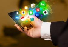 Hållande smartphone för hand med färgrika app-symboler Royaltyfri Foto