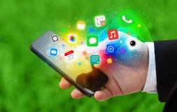 Hållande smartphone för hand med färgrika app-symboler Royaltyfria Bilder