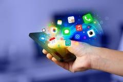 Hållande smartphone för hand med färgrika app-symboler Fotografering för Bildbyråer