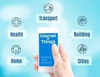 Hållande smartphone för hand med internet av ordet för saker (IoT) och a stock illustrationer