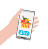 Hållande smartphone för hand med köpknappen och shoppingkorg som är full av sund organisk ny och naturlig mat arkivfoton
