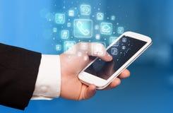 Hållande smartphone för hand med mobila app-symboler Royaltyfria Bilder