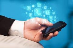 Hållande smartphone för hand med mobila app-symboler Royaltyfri Bild