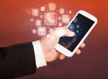 Hållande smartphone för hand med mobila app-symboler Royaltyfri Fotografi