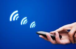 Hållande smartphone för hand med NFC-teknologi Royaltyfri Foto